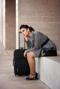 Bored pretty young Hispanic woman with roller suitcase